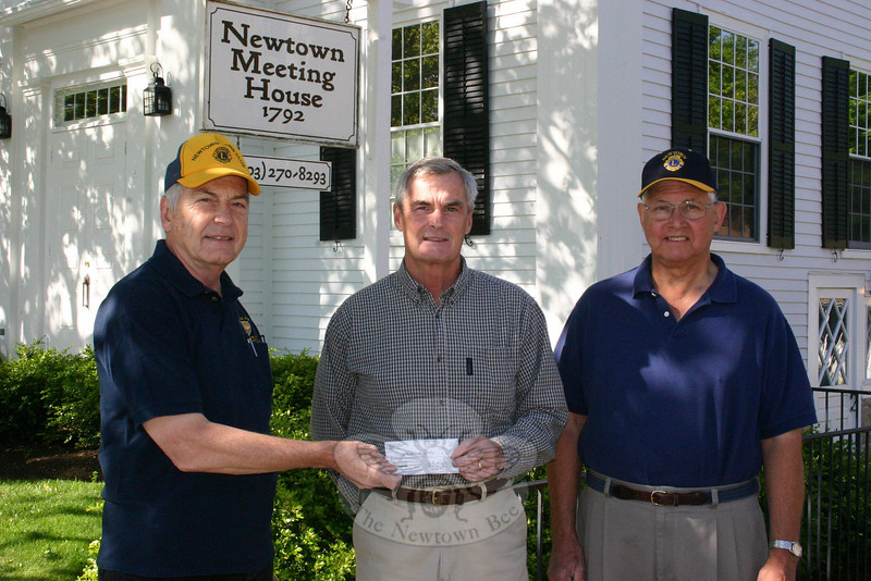 On May 15, prior to the changing of the winter to summer flag, Lions Club members Tom Evagash, left, and Kevin Corey, right, presented a check to Dave Lydem, who takes care of maintaining the Main Street flagpole and the flags it flies. (Hicks photo)