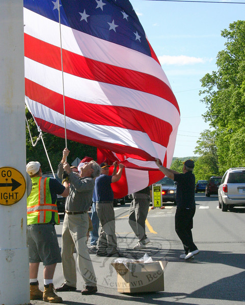 Newtown Lions Club, Hook & Ladder and Keeper of the Flag David Lydem brought summer to the center of Newtown on Saturday, May 15, with the raising of the summer flag on the Main Street flagpole. To the right of the pole is Hook & Ladder Firefighter Mike Aurelia. Next to him, also working the ropes to get the new flag up, is Newtown's Keeper of the Flag, Dave Lydem. (Hicks photo)