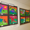 A colorful collection of paintings of fantastical dinosaurs filled a pair of bulletin boards, the output of second grade artists.  (Hallabeck photo)