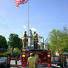 Newtown Lions Club, Hook & Ladder and Keeper of the Flag David Lydem brought summer to the center of Newtown on Saturday, May 15, with the raising of the summer flag on the Main Street flagpole.  (Hicks photo)