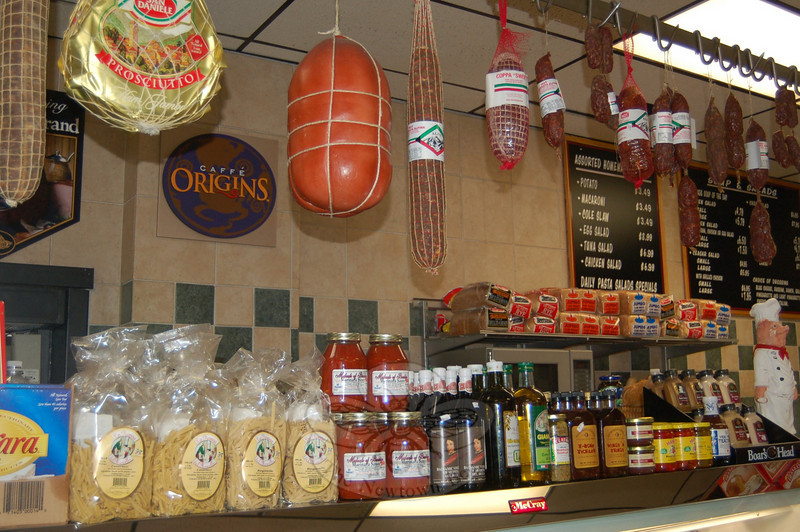Specialty items like Michael's pasta sauces from Brooklyn, San Pellegrino sparkling water, and handcrafted dried gnocchi are neatly stacked on racks in front of 26 feet of deli cases filled with hot and cold deli offerings and Boar's Head products at Newtown Deli & Catering.  (Crevier photo)
