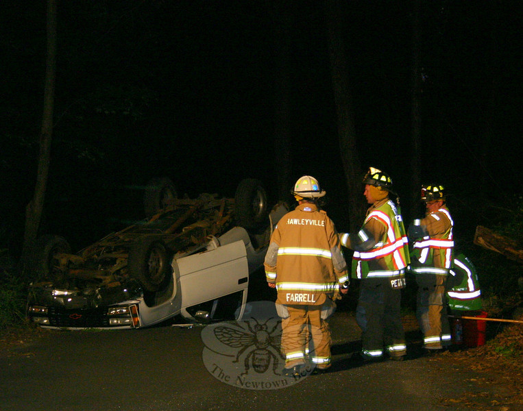 Hawleyville firefighters responded to a one-vehicle rollover accident about 2:08 am May 24 on Sturges Road. Police said motorist Craig Hayes, 23, of 40 Great Hill Road, was driving a 1990 Chevrolet GMT-400 pickup truck eastward near 15 Sturges Road, when he looked downward to operate the vehicle's radio and then looked back toward the road, but saw a deer on the road. Hayes swerved to avoid hitting the animal, but then struck an embankment, resulting in the truck rolling over onto its roof. Hayes climbed out of the vehicle and then jogged to his home, police said. Hayes received minor injuries in the accident and was evaluated by ambulance volunteers, but he refused treatment. Police charged Hayes with evading responsibility, making a restricted turn, and distracted driving. He is scheduled for a June 3 court appearance.  (Hicks photo)