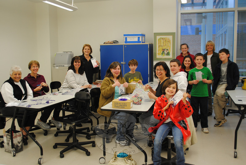 Kennedy Snyder (front center) is all smiles as she poses with members of the St Rose Kennedy Rosary Project at a recent evening of creating chaplets for free distribution at area imaging centers. The twine chaplets are allowed in MRI machines, and bring comfort to many patients.  (Crevier photo)