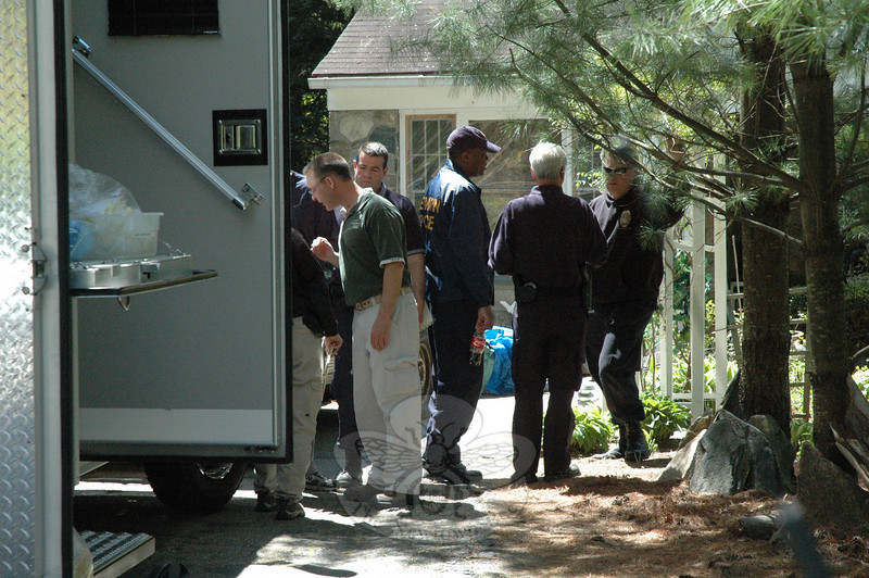 A group of town police and state police stand near the state's police major crime squad evidence collection van, which is parked in the driveway at 5 Keeler Road in Bridgewater where investigators executed a search/seizure warrant on April 29 in their investigation into the death of Elizabeth Heath.  (Gorosko photo)