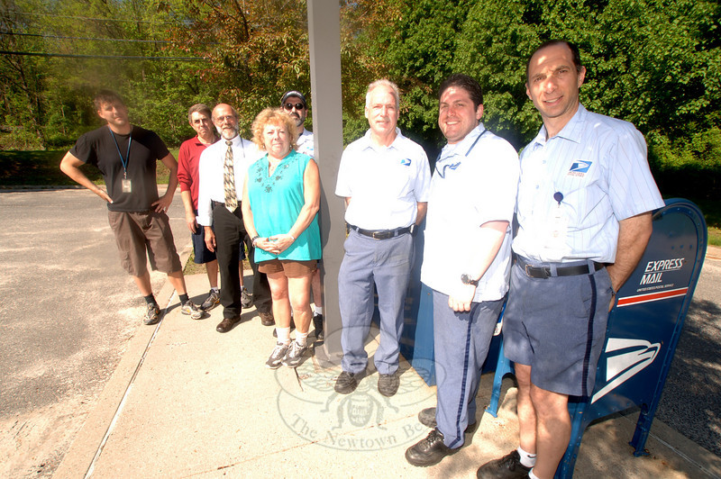 Taking a moment this week to remind residents to participate in the weekend's postal carrier's food collection to benefit Newtown Social Services' food pantry are, from left, Mike Sneideman, Tom Barbiero, Rich Crowther, Lynn Knapp, Chris Myers, John Ogrinc, Anthony Defranzo, and Dave Sabia.  (Bobowick photo)