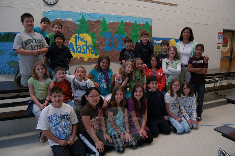 Sandy Hook School fourth grade teacher Carrie Usher's class performed an interactive skit for students during this year's One School, One Read kick-off assembly on Tuesday, April 27. The students and their teacher stand together with a sign they created depicting an Alaskan zoo.  (Hallabeck photo)