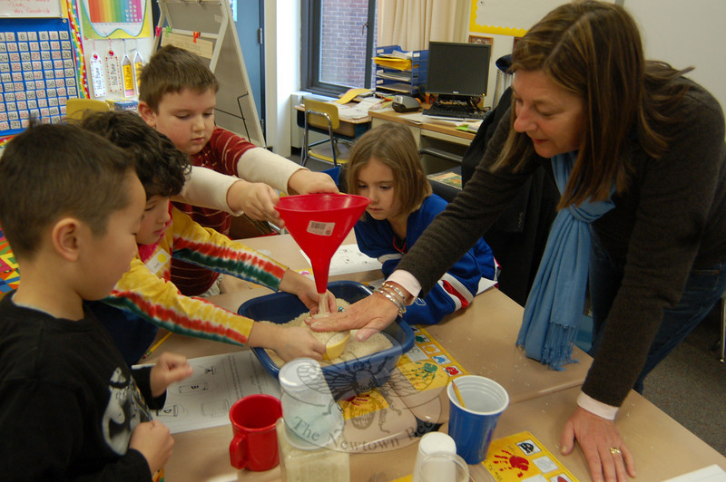 Head O'Meadow parent Karen Pelletreau helped students measure the capacity of objects by using rice on Measurement Morning at the school.  (Hallabeck photo)