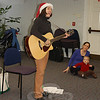 Singer-songwriter Francine Wheeler got into the holiday spirit with her shiny Santa hat and rollicking songs of the season on December 10 at C.H. Booth Library. Jessyca Tucker and son, Aidan, looking on, were two of nearly 50 caregivers and toddlers who attended the sing-along hosted by the library's children's department.  (Crevier photo)