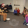 Singer-songwriter Francine Wheeler got into the holiday spirit with her shiny Santa hat and rollicking songs of the season on December 10 at C.H. Booth Library. Nearly 50 caregivers and toddlers attended the sing-along hosted by the library's children's department.  (Crevier photo)