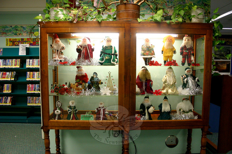 For untold years, Irene Thacker loaned examples of her handmade Santa Claus figures to the library during the holiday season. In 2004 Mrs Thacker donated a large portion of her collection, which she had been building for about 12 years, to the library's permanent collection. The Newtown resident died in March 2005, and the library continues to honor her memory with an annual presentation of her work. A display case in the Children's Department and another in the hallway outside that department will continue to show some of her whimsical and creative Santa Claus figures until the end of this month.  (Hicks photo)