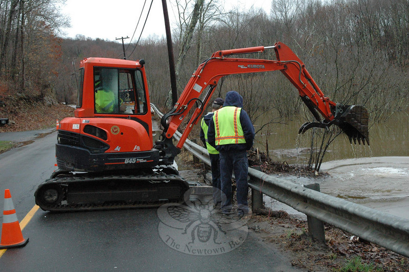 Members of the town's road crew used a small backhoe on Tuesday morning to unplug the entry point of a blocked three-foot-diameter drainage culvert that passes beneath Hanover Road. The activity of beavers in the area blocked the stormwater drainage pipe, which resulted in water flowing over Hanover Road after heavy rains on Monday night.  (Gorosko photo)