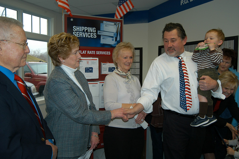 Postmaster Mark Favale, holding his grandson Reid, thanked Governor Rell for her support of the Hawleyville Post Office. Newtown First Selectman Pat Llodra, center, and former Newtown First Selectman Joseph Borst, left, look on.  (Crevier photo)