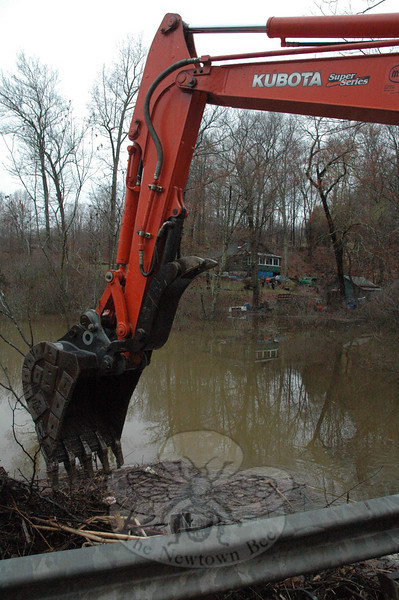 The house at 97 Hanover Road, which is framed by the arms of this backhoe, was cut off from Hanover Road on Tuesday morning after storm-related high water levels and beaver activity at an adjacent swamp caused the house's driveway to flood. A town road crew used the backhoe to open up a blocked culvert beneath Hanover Road, which then drained water from the swamp, restoring the residents' driveway access to Hanover Road.  (Gorosko photo)