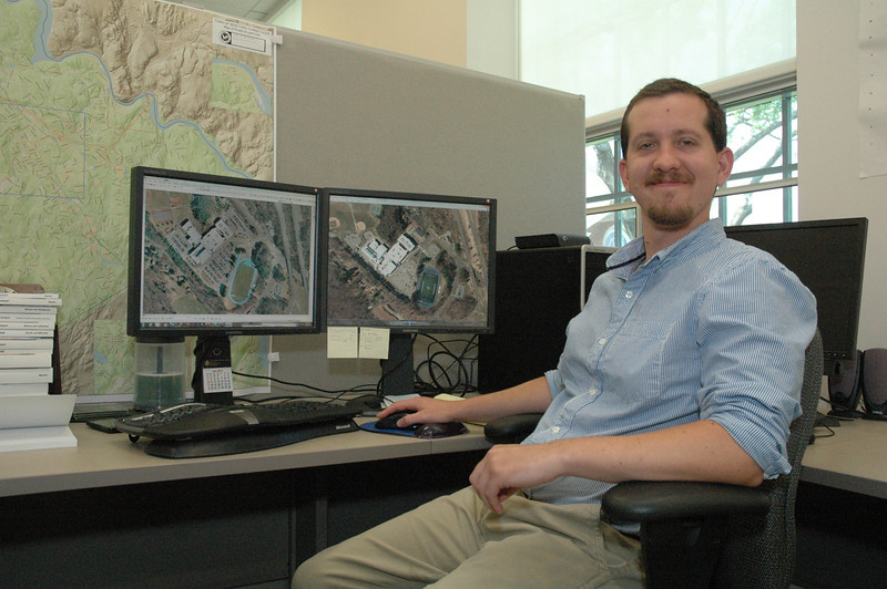 Steven Birney, the geographic information system (GIS) software specialist for the town's technology and GIS department, is shown at his desk at Newtown Municipal Center. Displayed on the dual computer monitors are overhead aerial views of the Newtown High School campus in 2007 on the left, and in April 2012, on the right.   (Gorosko photo)