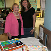 Children's Adventure Center Director Judy Sims, left, was joined by Laura Brosius, who is stepping in as chair of the CAC parent group, before dessert was served Friday night. A pair of cakes from Andrea's Pastry Shop were among the offerings for those who gathered to say farewell before heading off on their summer adventures.   (Hicks photo)
