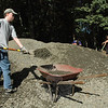 September 26, 2009: Members of Newtown Lions Club and Boys Scouts from Troop 270 and Troop 370 joined forces last Saturday morning to repair a deteriorated parking lot at the Orchard Hill Nature Center on Huntingtown Road. Jack Benedict, a member of Boy Scout Troop 270, repeatedly hefted crushed stone into a wheelbarrow to be distributed around the parking lot. Other Scouts and Lions Club members spread and smoothed the crushed stone to make an even parking surface. (Bee Photo, Gorosko)