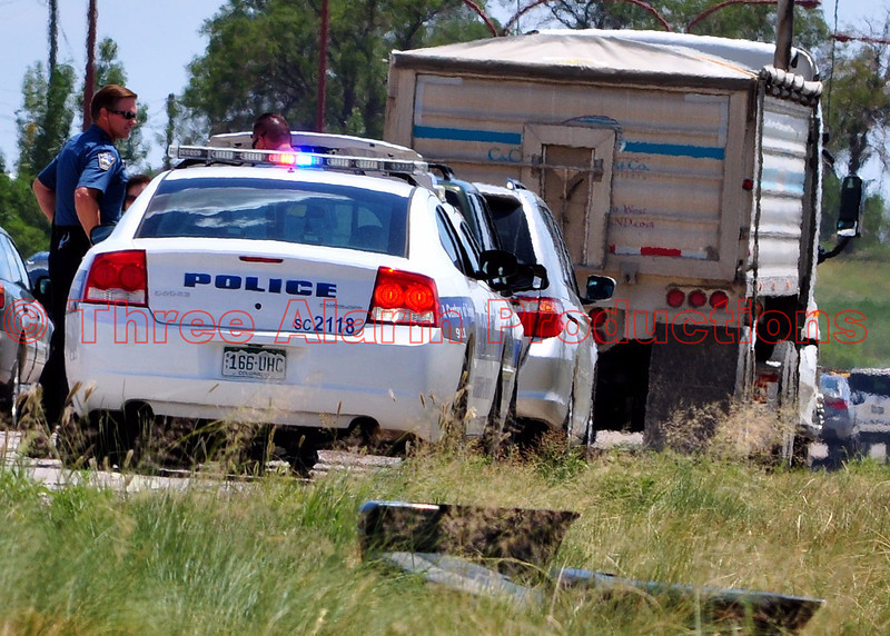 Colorado Springs Police Officers on the scene of a non-injury traffic accident, involving a tractor trailer vs. car on Southbound Powers Boulevard near Highway 24 in Colorado Springs, Colorado. The cars rear bumper came off during the accident, and can be seen in the grassy area.