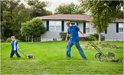 Wyatt Fritz, 4, left, helps his father Ash Fritz with the lawn chores outside their home in Shanksville, Pa. on Monday, Sept. 26, 2011.