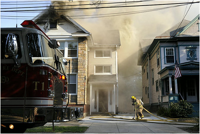 A member of the Erie Fire Department works the scene of two house fires on the 600 block of West 9th Street in Erie on Aug. 3, 2012.