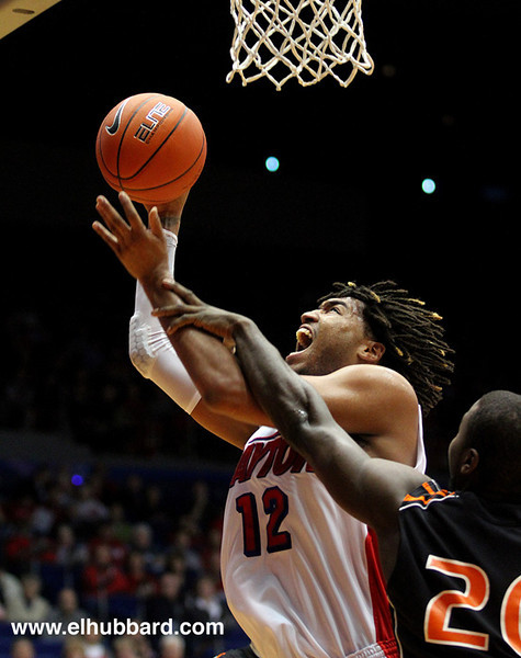 E.L. Hubbard photography<br /> University of Dayton forward/center Jalen Robinson puts up an offensive rebound for two as Findlay forward Jack Smith defends during their exhibition game at UD Arena in Dayton Saturday, Oct. 27, 2012.
