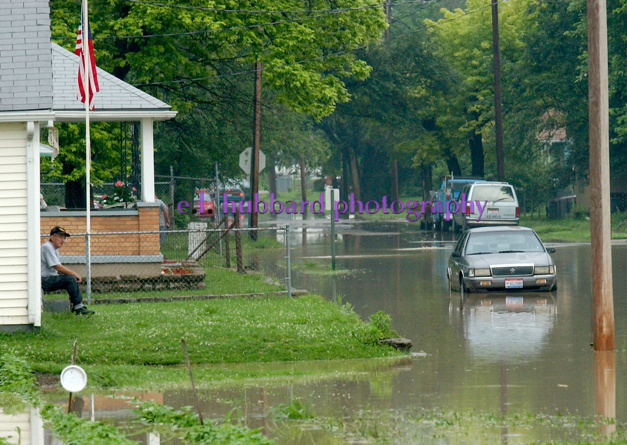 E.L. HUBBARD/JOURNALNEWS<br /> A New Miami resident takes it all in from his stoop as a car sits parked at the curb, surrounded by flood waters, Sunday, 6/15/03.