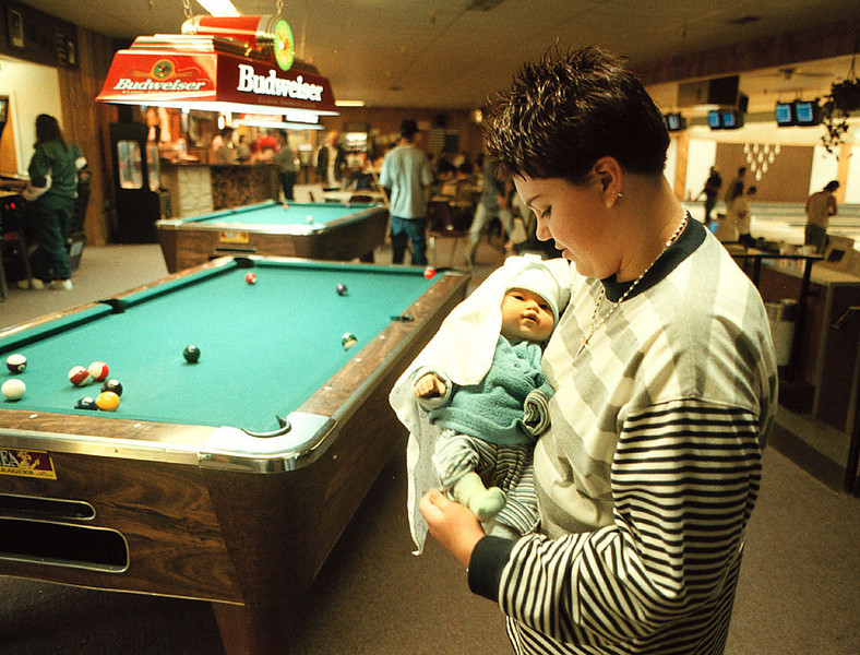 "Friday night at the neighborhood bowling alley Stephanie Larsen, 14, cradles Aliea, a ""Think It Over Baby."""