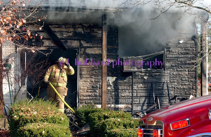 Smoke pours from the eaves of a house as a St. Clair Township((CQ)) firefighter stands in the front door while battling the blaze on Wichita Dr.((CQ)) Tuesday, 11/21/06. Staff photo by E.L. Hubbard