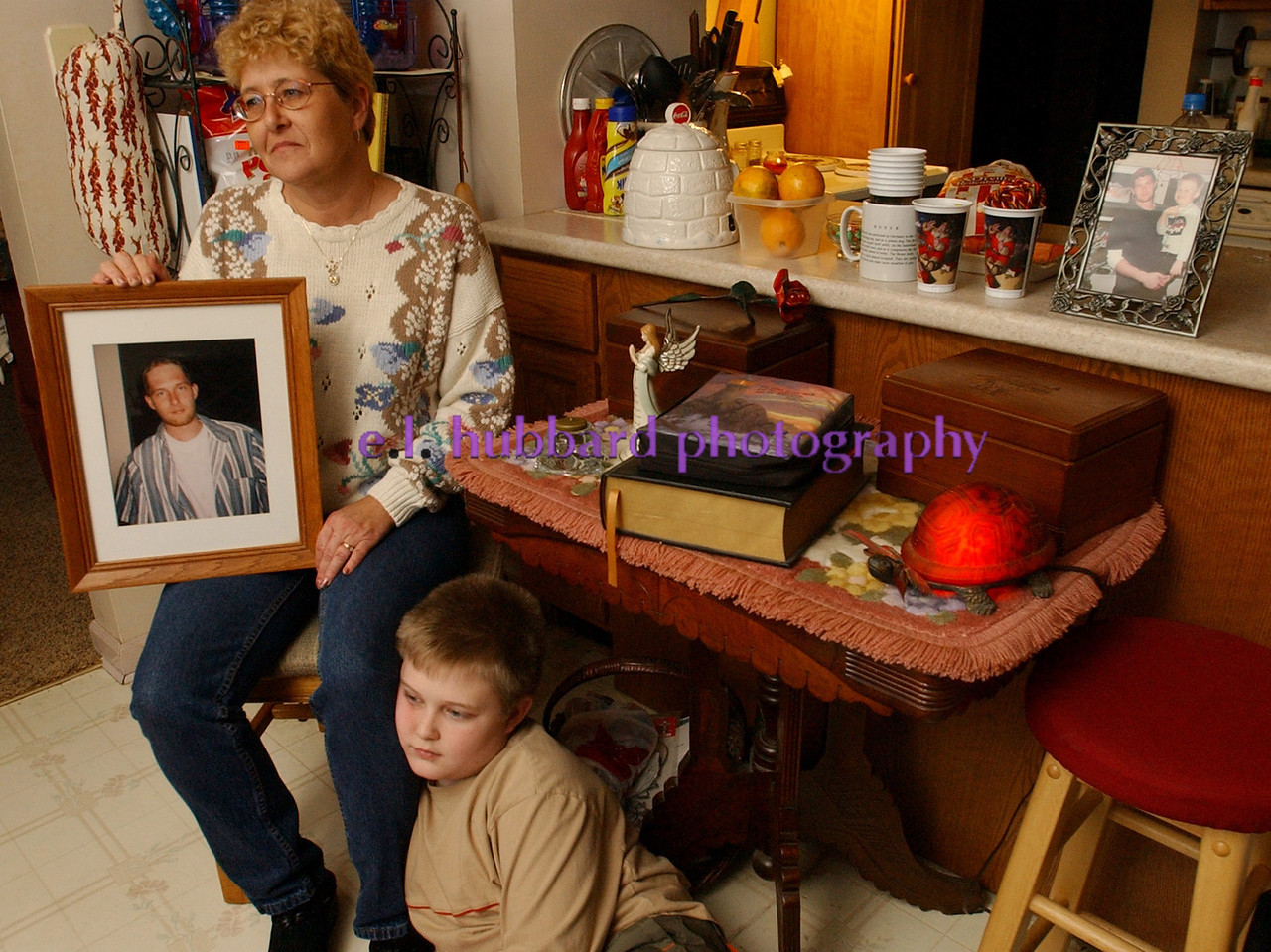 E.L. HUBBARD/JOURNALNEWS<br /> Cheryl Bartel and her grandson Jake Daniel Cooper, 10, in their Fairfield home Wednesday, 01/04/06 with pictures of Jon David Cooper, who was 25 at his death in 1999 and would have been 32 on Feb. 18. The box on the right of the memorial table contains the ashes of Jon David.