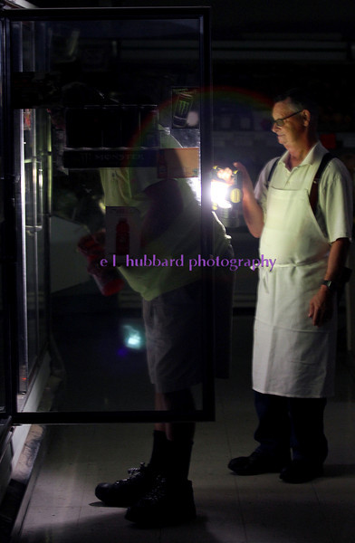 E.L. Hubbard photography<br /> Al Couch Farm Market butcher Donald Grathwohl holds a flashlight for Tim Bishop while Bishop shops at the store during the power outage in New Miami Sunday, July 1, 2012.