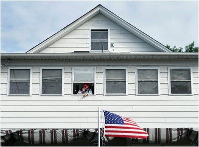 An American flag waves in the wind on Friday, Aug. 15, 2014, as John Young, 66, of Ocala, Fla., smokes a cigarette from the upstairs window of his brother Dan Young's house on East 31st Street in Erie where he is staying for the summer.