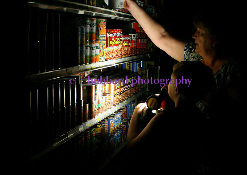 E.L. Hubbard photography<br /> A customer and her son use a flashlight to shop for groceries at Al Couch Farm Market during the power outage in New Miami Sunday, July 1, 2012.