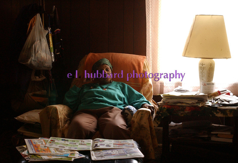 E.L. HUBBARD/JOURNALNEWS<br /> Alice Brown sits in the living room of her Front St. home Tuesday, 04/11/06, with only the sunlight of a window illuminating the interior. Brown, who has lived in the house for 37 years, said she is afraid she will soon be homeless if the City of Hamilton disconnects her utilities for an arrears she cannot afford to pay.
