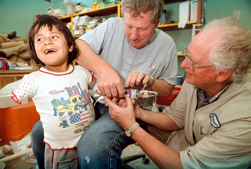 Photo by Bill Schaefer<br /> Jacquelin Yacha-Garcia, 7, smiles at her mother with anticipation while Randy Hamm, center, and Dave Lemmon, make final adjustments to her prosthesis. Jacquelin's right arm could not be fit for a prosthesis.