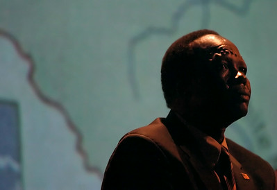 Simon Deng, sits in front of a map of Sudan, his native homeland and place of his former enslavement.  Monday evening at ECU's Hendrix Theatre he gave a lecture on 21st Century Slavery, bringing awareness and calling for change.  (Jenni Farrow)