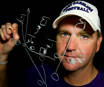 Skip Holtz, former East Carolina University head football coach, draws out a play.  Cover photo for football preview.