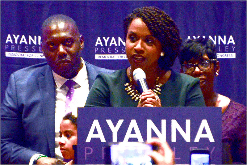 Ayanna Pressley addressing supporters as her husband, Conan Harris, and his daughter Cora, look on during victory celebration at IBEW Hall in Dorchester.