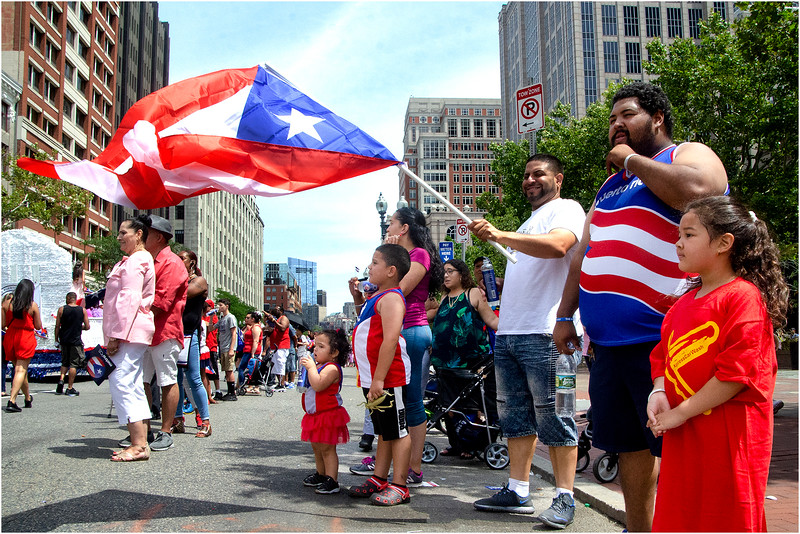 Casar Avila of Hyde Park waves the flag as the parade goes by on Boylston Street.