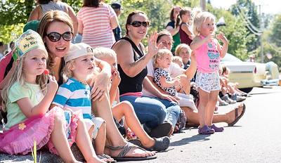 Greta Flynn, 4, left and her brother Briar, 1, watch Monday's Labor Day Parade in Buckfield with their mom Jordann.  The family from Turner joined hundreds who came to watch the parade and anxiously wait for candy to be thrown their way.  (Russ Dillingham/Sun Journal)