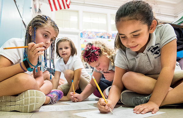 Saint Dominic Academy 3rd grade students work together on a word search puzzle Wednesday morning during the first day of school at the Lewiston elementary school campus.  Clockwise from left to right are: Maddy McGonagle, Zoey Cote, Mirabel Patrick and Abigail Martin. (Russ Dillingham/Sun Journal)