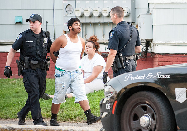 Lewiston Police Officer Spencer Simoneau takes a man into custody at the corner of Bradley and Pine Streets in Lewiston Tuesday evening. (Russ Dillingham/Sun Journal)