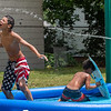 Jaice Addison, left, reacts after his water gun ran dry while squirting his cousins in Auburn Monday morning. His other cousin, Marcade Patrick, middle, hides in their pool after Bradley Patrick, right, picked up the hose fillling the pool as they try to stay cool during Monday's opressive heat.