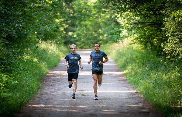 Ryan Smith, left and Robbie Hollis jog down the Whitman Spring Road Trail in Auburn Thursday night August 1, 2019 before a training run.