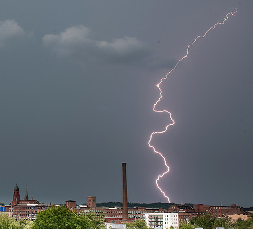 A bolt of lightning strikes behind the Lewiston skyline as people in Festival Plaza in Auburn, foreground, were packing up and clearing out after the storm cancelled National Night out in Auburn.  (Russ Dillingham/Sun Journal)