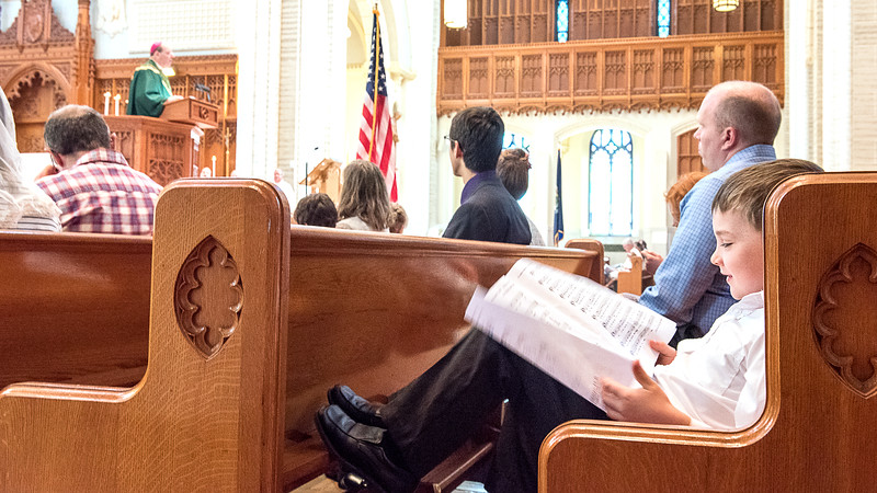 Lucien Barnard, 5 of Lisbon Falls, looks at songs in the program as Bishop Deely gives the sermon during Sunday morning's Blue Mass. (Russ Dillingham/Sun Journal)