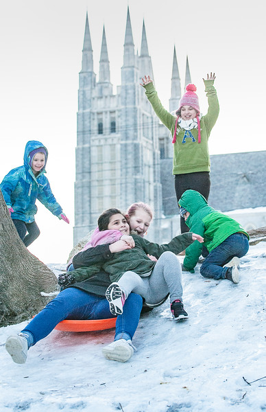 Madyson King, 11, sitting on a sled holds on to her friend, Aylah Valliere, 8 (grey sweatpants) as other friends and siblings cheer and wait for their turn on the one sled they were sharing to slide down a hill in an empty lot off Howe Street in Lewiston Thursday afternoon.  The spires of Basilica Saints Peter & Paul rise in the background.  (SUN JOURNAL PHOTO BY RUSS DILLINGHAM)