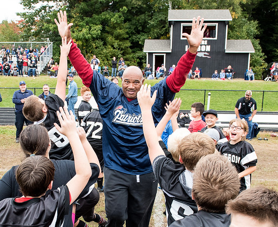Members of the Lisbon Youth Football program jump to give former New England Patriots player Garin Veris a high five as he is introduced at Thompson Field at Lisbon High School Sunday afternoon during the biannual Lisbon Police DARE Program fundraiser.  Several former players and friends took on a team comprised of local police and augmented with other members of the community.  (Russ Dillingham/Sun Journal)