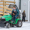 """Gary Simard, right,  talks to his grandson Grayson Bowie as he sprinkles sand as his other grandson Owen, drops the plow blade while his mother Allison steers as they clean snow from Simard's Auburn driveway Wednesday.  The Bowies are from Poland and were in town for a dentist appointment and brought their schoolwork to do remote classes in the morning and for """"recess"""", they got to help work outside."""