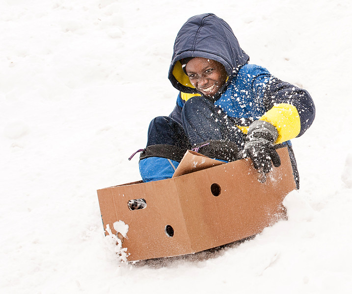 While most everyone sledding on the hill at Paradis Park on Pierce Street in Lewiston was using a sled, Adrizak Raheem, 14, and other firends from Lewiston, used trash can lids, laundry baskets, and whatever they could find Sunday afternoon. (Russ Dillingham/Sun Journal)