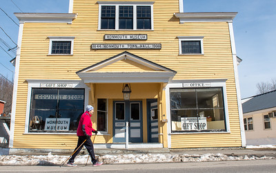 """Ann Leclair takes a walk down Main Street in Monmouth, Maine Wednesday afternoon, March 25, 2020.  """"It is so nice out today I needed to get out and breath some fresh air.  I am very worried about this virus, especially waiting to get a call from my daughter who is a doctor telling me she has a fever."""" said Leclair as she passed walked through downtown."""