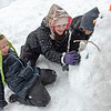 Ella Lutz, left, cracks up laughing as she and her sister Mallory, center, joke about their carrot head snowman they were building in front of their home on Hampshire Street in Auburn, Maine on Thursday afternoon, January 16, 2020.
